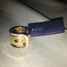NEW BCBG GOLD BUCKLE RING WITH RHINESTONES SIZE 6 Gorgeous and eye catching BCBG gold ring crafted to resemble a belt buckle. Very popular right now especially with the sparkly rhinestones! New with tags, never worn, and Size 6. Contact me with questions! BCBG Jewelry Rings