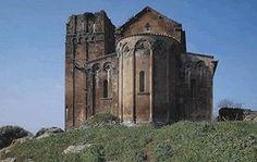 Ozieri - Chiesa di Sant'Antioco di Bisarcio. Nell'edificio si distinguono tre tempi di fabbrica: all'impianto dell'XI secolo risalgono i filari di cantoni appena sbozzati, alla base delle murature dei fianchi verso E. La seconda fase edilizia, successiva alla metà del XII secolo, è caratterizzata da cantoni di media pezzatura ben sagomati. Il portico fu aggiunto agli inizi del XIII secolo. La parte sinistra del portico, crollata, fu ricostruita nel XVI secolo.