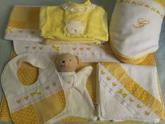 Conjunto constituído por lençóis e colcha de alcofa, babete, fralda de algodão, naninha, toalha de banho, envelope para a roupinha, babygrow e roupinha interior.