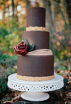Brides.com: 22 Wedding Cakes for Dark, Modern Color Palettes. A Romantic, Three-Tier Chocolate Fondant Wedding Cake. We love the understated elegance of these soft chocolate fondant layers, and that gorgeous, single red sugar rose on the middle tier. Plus, the tasteful gold trim on this luscious cake from Wild Orchid Baking Company is refined and simply lovely. See more brown wedding cakes.
