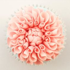 Close-up of a sugar dahlia perched atop a cupcake  Made with florist paste by rolling up little circles and arranging them around a closed bud. #faircake #cakeschool #cakeclass #cakecourse #cakecourses #cupcakecourse #Greenwich #London by faircake
