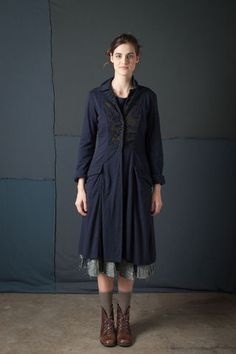 """100% organic medium-weight cotton jersey Ezra Coat with placement negative reverse appliqué in our Magdalena stencil. Flares slightly at the waist and features crocheted snap closures and pockets that sit below the hip. Measures 42"""" from shoulder. Shown here in Navy and Black. Center front panels come in Black; choose your coat color below. Please allow four to six weeks for delivery. Wash gently + Hang to dry. Free domestic shipping. Made in the USA."""