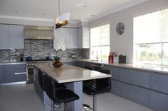 Modern kitchen remodel features grey and cream color palette, large center island with quartz counter, glass and stone backsplash, hand wrought custom pendant light and textured floor tile.  #ranchointeriordesign.com