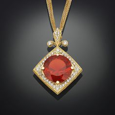 The heat of a magnificent Mexican fire opal is perfectly balanced by 55 glistening white diamonds totaling 0.70 carats in this eye-catching pendant. Weighing a dazzling 8.04 carats, this extraordinarily rare opal displays the signature radiant tangerine orange hue for which this unique stone is known. Set in 18K yellow gold. Mexican fire opals are singular among the world's opals for their bright and almost uniform color.