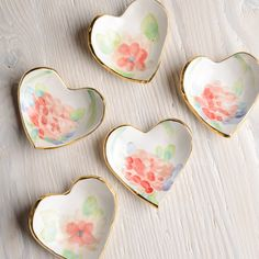 """Susan+Gordon+Watercolor+Floral+Heart+Ring+Dish+-+Go+ahead,+give+your+heart+away...or+keep+it!+Sweet+and+simple,+these+popular+heart+dishes+look+completely+charming+on+your+nightstand+or+vanity.+An+easy+gift+for+a+loved+one,+or+yourself,+to+create+smiles+year+round.  4""""+W+x+4""""+D+x+1""""+H Handmade+with+white+stoneware+pottery+and+glazed+with+high+fire+glaze Each+piece+is+handpainted Features+22K+gold+luster+overglaze Not+food+safe,+hand+wash Due+to+handmade+nature,+each+piece+will+vary+sl..."""