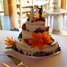 Naked Cake with fresh Strawberries, Blackberries, Raspberries and Blueberries. Oval shape ~ Gorgeous huge Orange Lillies! Top Tier Wedding Cakes - Medford, Oregon