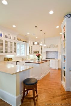 A lovely white cottage kitchen with glass cabinets, wood floors, a beautiful wood hood, and an island with pendant lights.     #3 in Traditional White Kitchen Cabinets