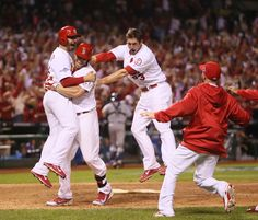 St. Louis Cardinals' Daniel Descalso (left) jumps into the arms of teammate Matt Holliday after scoring the game-winning run on a single by Carlos Beltran in the bottom of the 13th inning during Game 1 of the National League Championship Series between the St. Louis Cardinals and the Los Angeles Dodgers on Friday, Oct. 11, 2013, at Busch Stadium in St. Louis. Also celebrating are David Freese (second from right) and Shane Robinson (far right.) (AP Photo/St. Louis Post-Dispatch, Chris Lee)