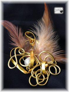 Broche en hilo de aluminio dorado,combinando dos formas distntas,como motivo una bola de resina y plumas en tonos marrones