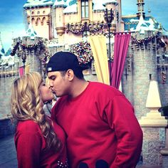 Disneyland couple kissing in front of Sleeping Beauty Castle