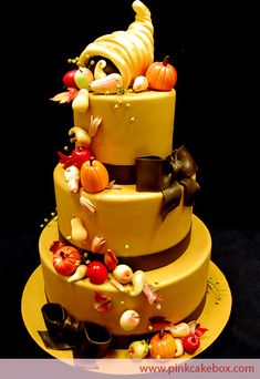This three tier cake is a perfect centerpiece for a thanksgiving dinner. It's topped with a cornucopia that is filled with pumpkins, apples, pears, and s