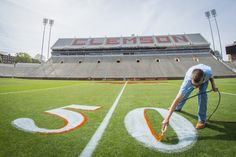 https://flic.kr/p/FVR2Eg | Painting the 50 yard line | Brad Justice, a member of the Clemson University field crew, adds a Clemson orange outline to the 50 yard line in preparation for the upcoming Spring Game and the opening of the 2016 football season, April 6, 2015. (Photo by Ken Scar)