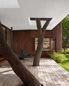 Mooie combinatie van modern en landelijk. Wit gestuukt plafond en strakke vlonder worden doorbroken door bomen. Lakeview Residence / Alterstudio Architecture