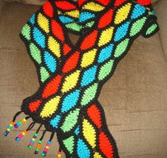 Three ounces of Caron Simply Soft Brites are used in a variety of colors to produce this beautiful Stained Glass Scarf. When looking at this crocheted scarf pattern it reminds us of the stained glass windows in a church.