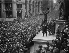 Actor Douglas Fairbanks holding up actor Charlie Chaplin in front of  a crowd   to promote Liberty Bonds, Lower Manhattan, NYC.