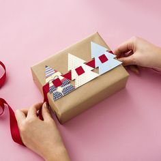 Want to dress up plain wrapping paper? Check out this DIY for easy holiday present toppers made from recycled holiday cards. #partner