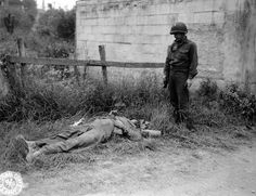 U.S. Army Technical Sergeant Joseph C. Self looks over the body of a dead German sniper in a small village just days after the Allied Landings in Normandy. Saint-Laurent-sur-Mer, Calvados, Lower...
