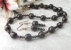 This Brown Pearl Jewelry Set is made with pearl and crystal. It is a stunning necklace and earring set that has deep, dark, chocolate brown