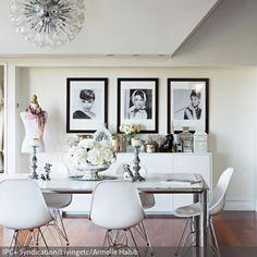 Eine Prise Hollywood-Glam bringen die Porträts von Audrey Hepburn in dieses Esszimmer. Die weißen Eames-Chairs und die Schneiderpuppe als Dekoration sorgen für…