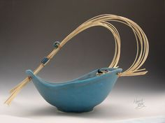 "Thrown and altered basket with natural reed handle and clay beeds in turquoise mat glaze, 13"" high,12"" diam."