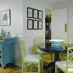 Fun blue & green dining room design with gray walls, chair rail, blue zen Asian cabinet, glossy black pedestal table, green Jonathan Adler faux bamboo chippendale chairs and art gallery.