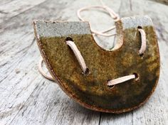 Handmade ceramic clay necklace with leather lace stitch effect provides the perfect balance of organic and modern cool. Ceramic pendant is shaped like an upside-down horseshoe (for good luck!) and has layered tones of ombre green and gray with a natural leather lace string woven through the middle. Necklace is made from soldate clay and high fire glaze. Kiln firing leaves the piece sturdy, but make sure to still handle with care.  Necklace length is adjustable up to 15 inches, with a slip…