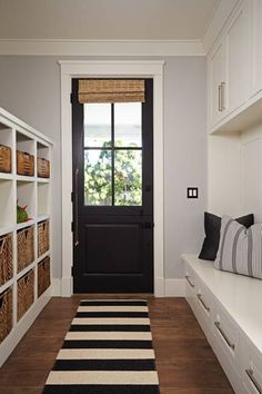 black paint and decorating ideas for doors Fun back entrance/mudroom with tons of storage, in drawers and overhead cabainet above below seating, note soft grey wall, the natura lsahde on door echoes storage baskets; pillows on built-in benches echo grey in walls, bold b/w rug ties together but could be replaced by solid color to give different feel to room