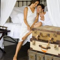 Create the look of a four-poster canopy bed with curtains and curtain rods hung from the ceiling.