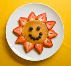 Comida divertida para niños. Panqueques con frutillas y arándanos.