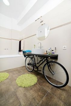 An unused bicycle replaces the sink cabinet under the black countertop with vessel sink and toiletries