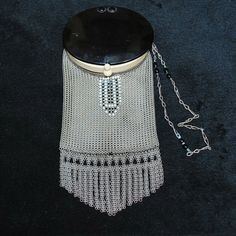 1920s Whiting and Davis purse features a black celluloid compact top with a mirror inside. The body is made of fine ring mesh with a black and white drop.  3.5 x 8 inches including fringe.