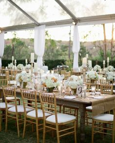 Full centerpieces of pee gee hydrangea, David Austin garden roses, Queen Anne's lace, and dusty miller topped long farmhouse tables.