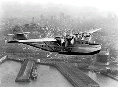 The China Clipper passes over the San Francisco waterfront. The aircraft completed the trip in six days, with a flying time of 59 hours, 48 minutes. Overnight stops included Honolulu, Midway, Wake Island, and Guam.