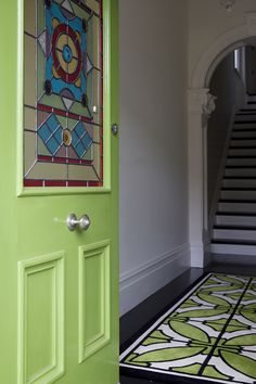 A lovely stained glass window in a bright apple green coloured door and matching entry rug in the foyer.