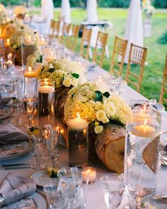 Rustic logs of white birch with hollowed-out holes get a sweet touch from arrangements of white hydrangea and tall vessels filled with water and floating candles.