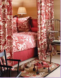 A bed enclosed by toile fabrics provides a cozy sleeping nook