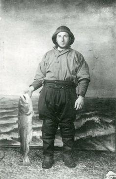Beugvisser Abraham Bot poseert tegen de kunstmatige achtergrond van een woest golvende zee in de studio van een onbekende fotograaf. Hij houdt een grote vis [kabeljauw?] vast in zijn rechterhand. Hij is gehuld in visserskleding. In zijn rechteroor draagt hij een oorbel. ca 1915 foto #ZuidHolland #Vlaardingen