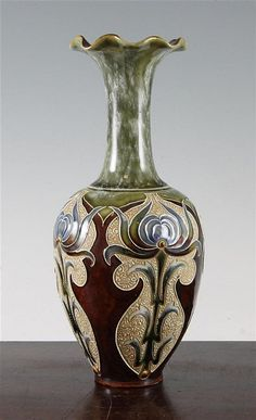 A Doulton Lambeth Art Nouveau stoneware vase, by Eliza Simmance, c.1900, the lobed ovoid body slip trail decorated with stylised flowers on a brown ground, the green and white mottled neck with wavy rim, impressed and incised marks, 10in.