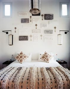 A collection of stamps displayed above a bed dressed with a Moroccan wedding blanket
