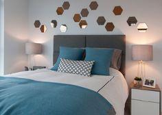 chambre grise avec des miroirs décoratifs et coussins en bleu sarcelle