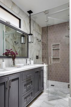 This beautiful bathroom features gray and white marble that continues from the floor to the backsplash and shower. This marble meets a wall of taupe hexagonal tile for an attractive design transition. A gray double vanity completes the stylish look.