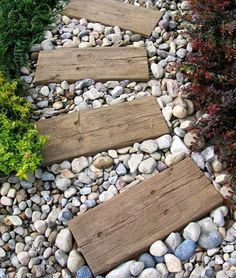 Cute yard or garden path idea. Wood planks with river stone. Simple and pretty.