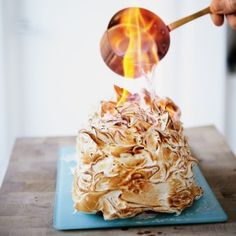 A meringue dessert with flaming alcohol being poured over it