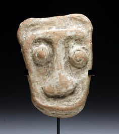 A Pre-Columbian Marajoara Mask, Marajo Island, Para Brazil, ca. 400-1300 A.D. Redware pottery maskette, evidently from a very large vessel, in abstract human form, intact and with light root marks and deposits.
