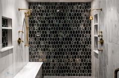Elegant walk in shower is located behind a seamless glass enclosure and fitted with glossy black grid floor tiles and a black and gold beehive tiled accent wall.