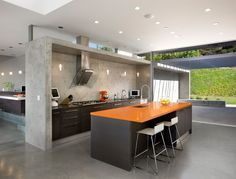 """modern concrete kitchen - the orange countertop is the perfect colour accent to add """"zhush"""" to the space..."""