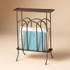 "WROUGHT IRON TRAY TOP MAGAZINE RACK -- A slim iron table with a magazine rack, to tuck beside an easy chair, beneath a window, inside an entryway. The top is wide enough to hold a reading lamp or potted plant, while the graceful arches below will stash newspaper and novel, mail and the like. Handmade in Mexico; size will vary slightly. 16""W x 21-1/2""H. Table top is 5""D; base is 9-1/2""D."