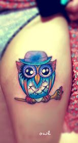 A colorful cute owl wearing a har tattoo on the thigh