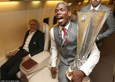 Paul Pogba keeps a tight grasp on the Europa League trophy as his Manchester United manager Jose Mourinho watches on