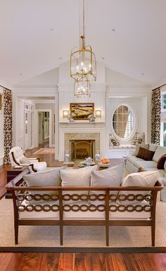 A stunning traditional great room with a white loveseat, sofa and armchair. The Anderson Studio of Architecture & Design.